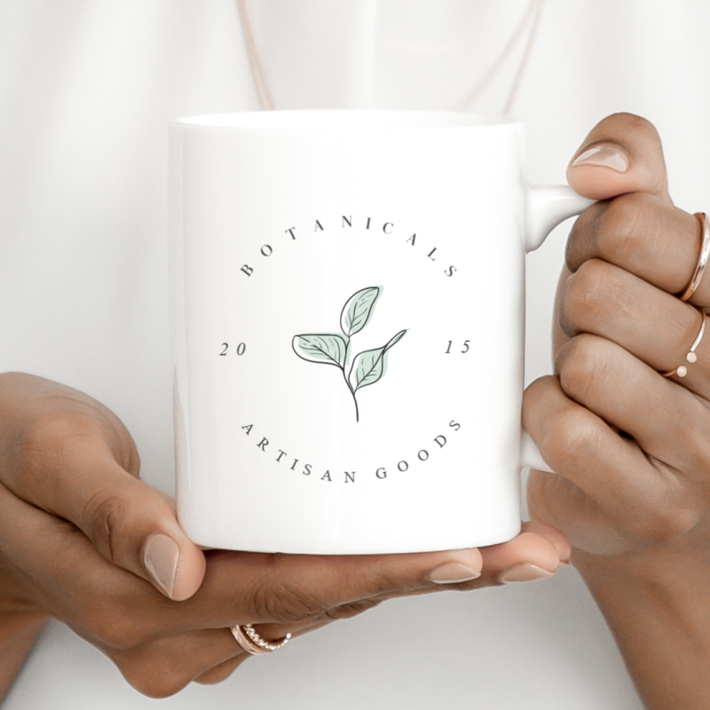 """""""Botanicals Artisan Goods"""" curved text design on coffee cup."""