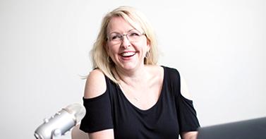 Social media marketing expert Brenda Ster sitting behind laptop.