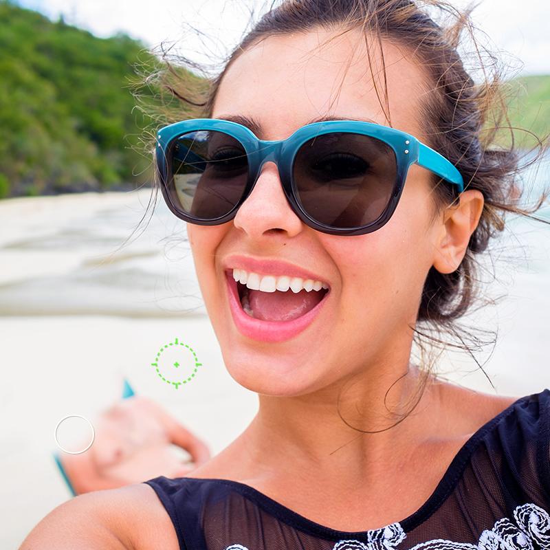 Femme souriante sur la plage avec un homme en arrière-plan en cours d'effacement à l'aide de l'outil Clone de PicMonkey.