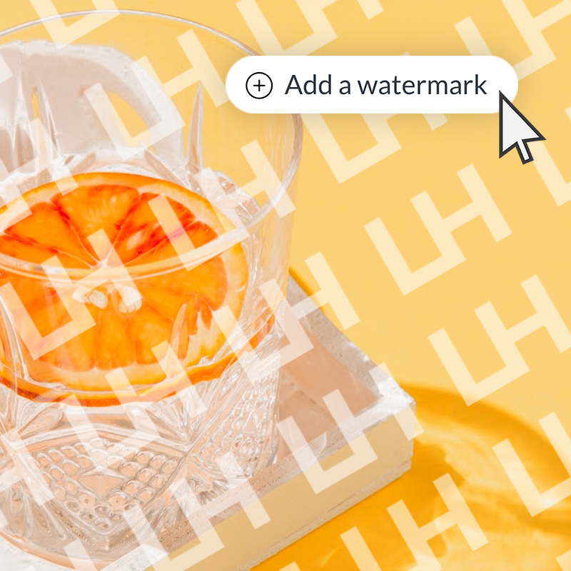 """Empty glass with orange slice in it and tiled watermark pattern over entire image, highlighting that you can """"Add a watermark"""" to your designs in PicMonkey."""