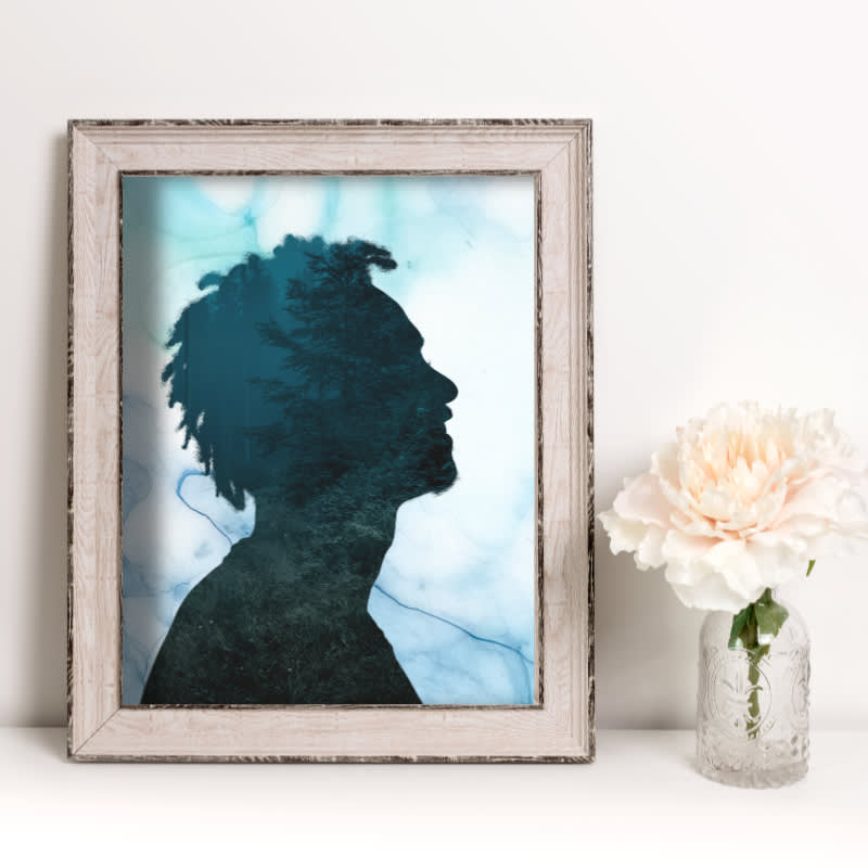 Double exposure silhouette photo placed inside a frame next to a flower vase
